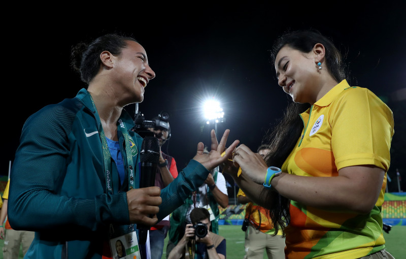 RIO DE JANEIRO, BRAZIL - AUGUST 08: Volunteer Marjorie Enya (R) proposes marriage to rugby player Isadora Cerullo of Brazil after the Women's Gold Medal Rugby Sevens match between Australia and New Zealand on Day 3 of the Rio 2016 Olympic Games at the Deodoro Stadium on August 8, 2016 in Rio de Janeiro, Brazil. (Photo by David Rogers/Getty Images)