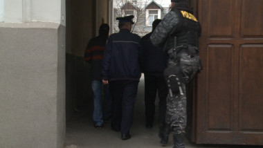 politisti aduc un suspect la DIICOT