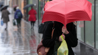Femeie umbrela rosie ploaie frig meteo vremea - Guliver Getty Images-1