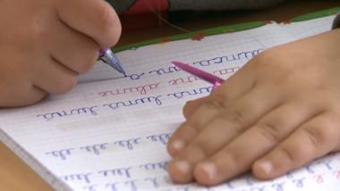 copil scrie caiet maini