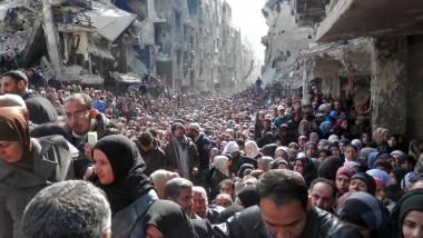 aglomeratie de oameni printre ruinele din siria.