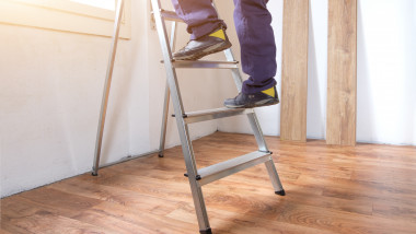 Feet of a carpenter ready for work on a ladder