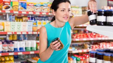 Woman choosing jar of fruit jam