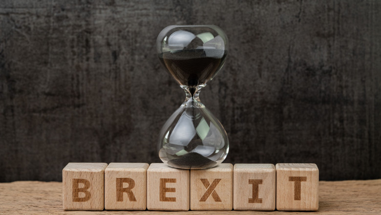 Brexit, time countdown for the UK to deal and withdraw from Euro zone concept, sandglass or hourglass on wooden cube block with alphabet building the word BREXIT on wood table, dark black background