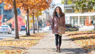 Young happy woman on sidewalk street walking in Washington DC, USA United States in alley of golden orange yellow foliage autumn fall trees on road during sunny day