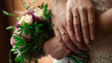 hands of the bride and groom with wedding rings, bride holds a wedding bouquet in hands, the groom hugs her from behind