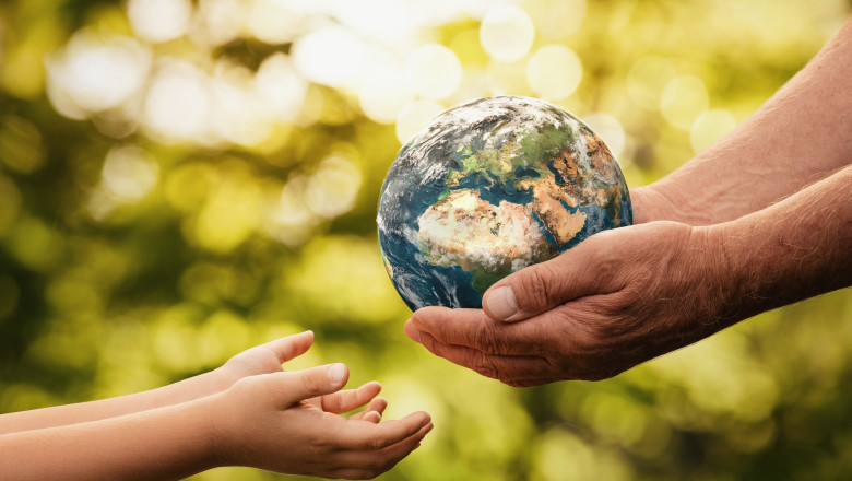 Senior hands giving small planet earth to a child