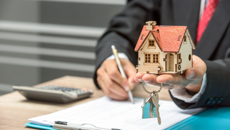 business man hand key and house model