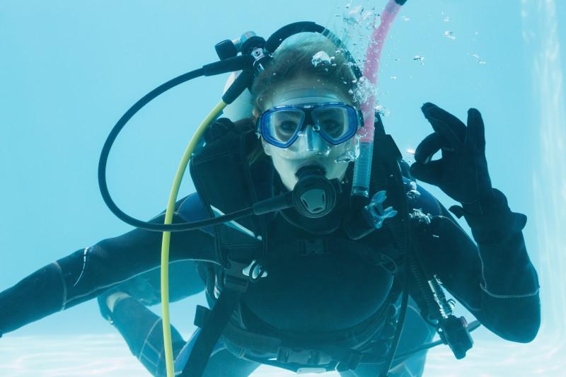 Woman on scuba training submerged in swimming pool making ok sign