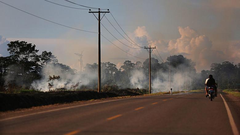 motociclist pe un drum pustiu, acoperit parțial de fum produs de incendiu de vegetație, imagine apocalipsa meteo, schimbări climatice
