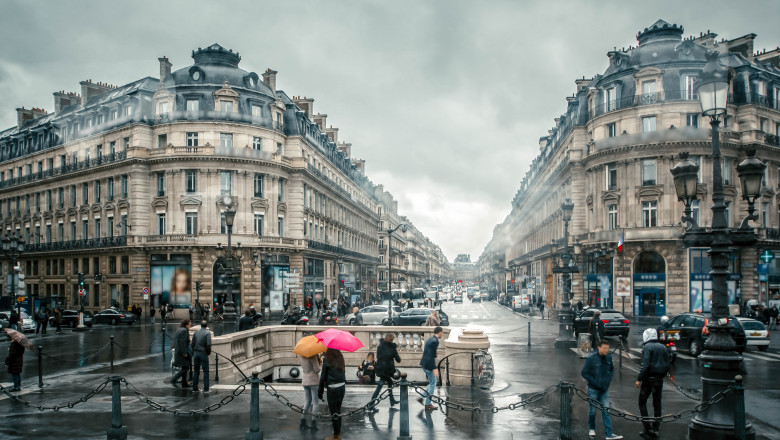 People under colored umbrellas run in the rain on the streets of Paris, France