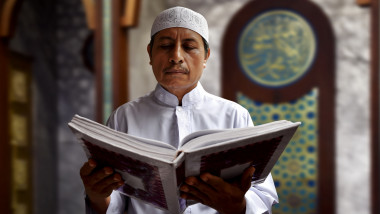 Old muslim man reading koran in mosque