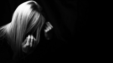 Depressed woman hiding her face in a dark