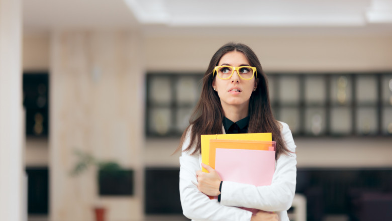 Confused Businesswoman Holding Paperwork in Office Building