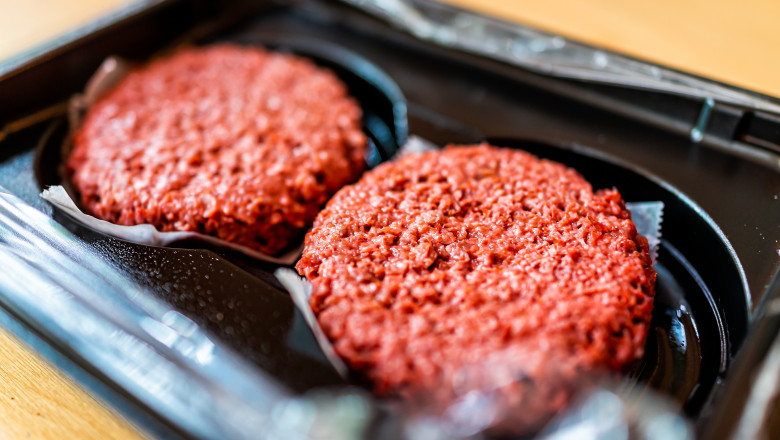 Closeup of two raw uncooked red vegan meat burger patties in plastic packaging