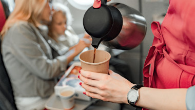 Air hostess is making coffee for passengers