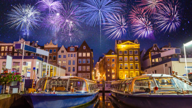 Traditional old buildings and boats with fireworks in Amsterdam, Netherlands