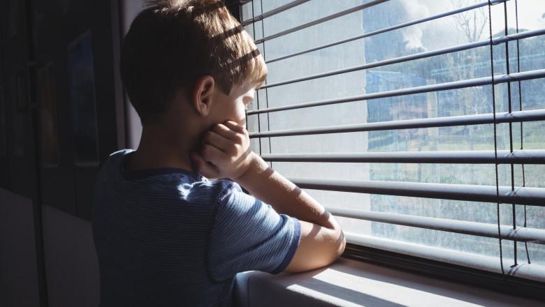 copil trist abuz fereastra casa familie