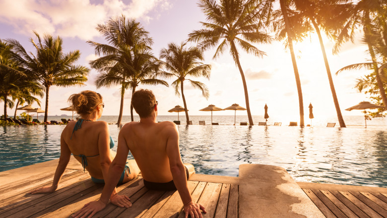 Couple enjoying beach vacation holidays at tropical resort with swimming pool and coconut palm trees near the coast with beautiful landscape at sunset, honeymoon destination