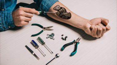 cropped view of man repairing metallic mechanism in arm with screwdriver
