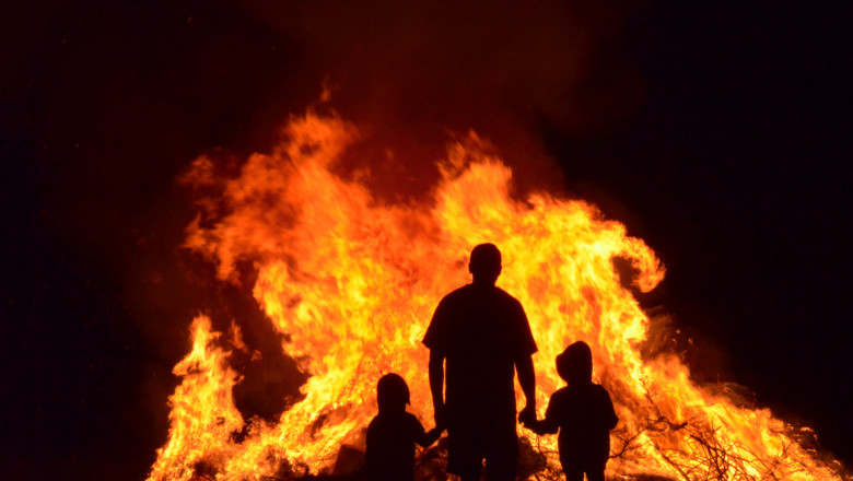 Man and children in silhouette watching the flames of a huge bonfire.