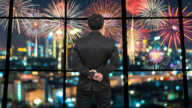 Back side of Businessman looking at Fantastic fireworks on the photo blurred of cityscape at night scene background,Business and holiday concept