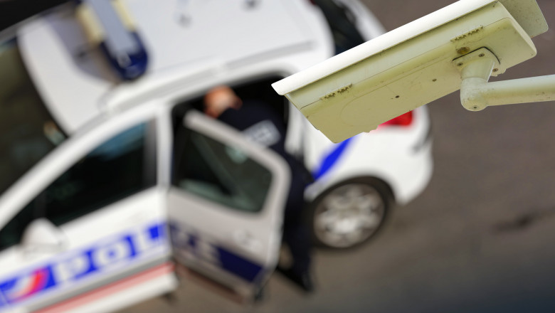 security CCTV camera or surveillance system with police car on blurry background