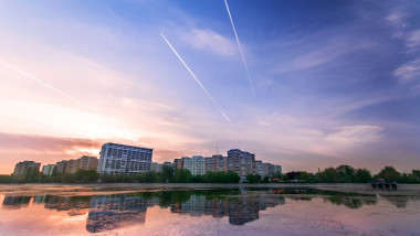 Morning cityscape at sunrise near a lake with reflection and plane streaks in the sky