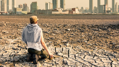 A man in the desert looks at the city after the effects of global warming