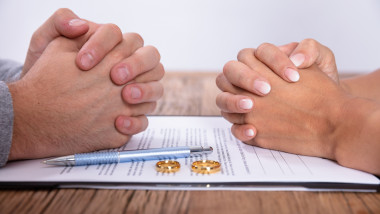 Couple's Hand With Divorce Agreement And Wedding Rings