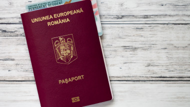 Romanian passport with american green card on wooden background. Population exodus from romania concept.