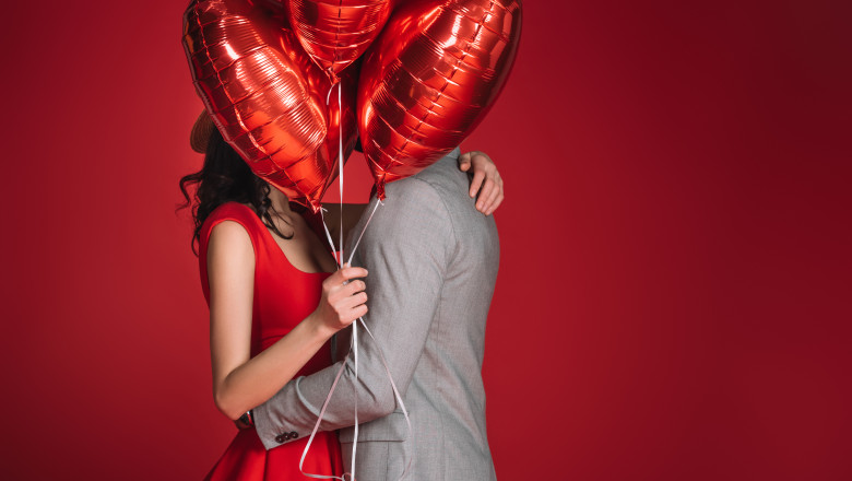 couple covering faces with bundle of balloons isolated on red