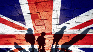 Conceptual shadows of group of people walking through the streets with painted United Kingdom flag on the floor.