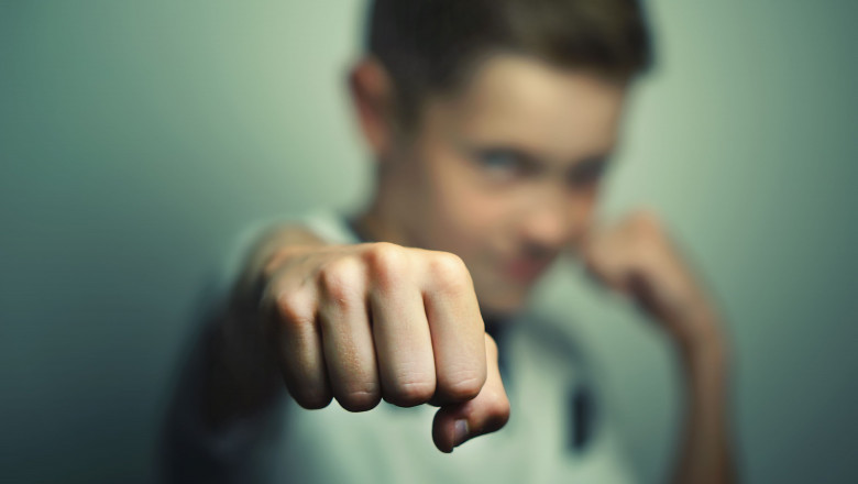 Angry child boy in white t-shirt training box punch.