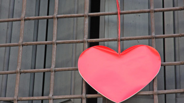 red heart hanging on the grid of a window outside a building on Valentine's day