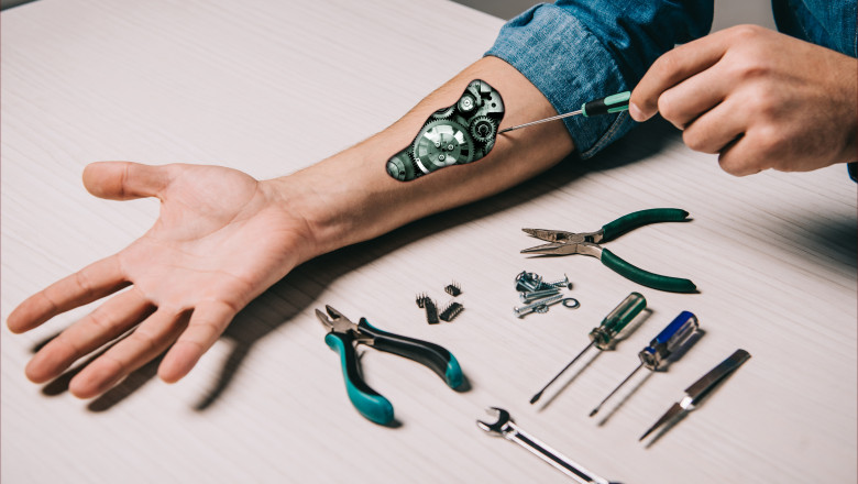 cropped view of man repairing metallic mechanism with screwdriver and pliers