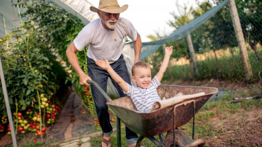 Happy grandfather and his grandson in garden