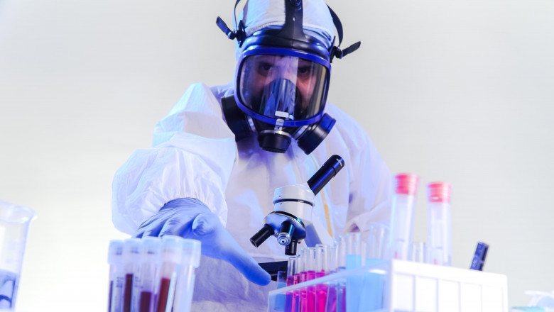 "coronavirus epidemic and infectious diseases concept""nmale lab technician doing research in the lab with protective suit and gas mask."