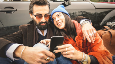 Hipster couple having fun with mobile smart phone at car roadtrip - Friendship concept with best friends connecting and sharing content on social media - Millennial generation as fashion influencer