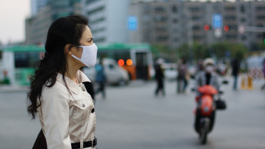 O femeie poarta masca pentru a se proteja impotriva bolilor si a poluarii