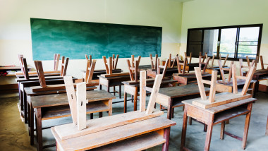 chair and table in class room with black board background, no student, school closed concept