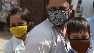 Un barbat si cei doi copii ai sai poarta masti pentru a se feri de coronavirus, in Iran