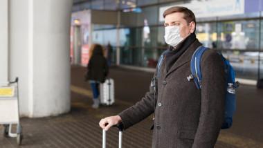 Barbat cu amsca, in aeroport, pentru a se proteja impotriva bolilor si a poluarii