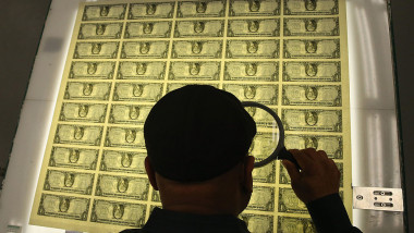 om se uită la bancnonte de 1 dolar cu lupa