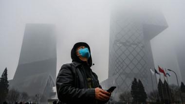 Un barbat din China se protejeaza impotriva poluarii prtand o amsca
