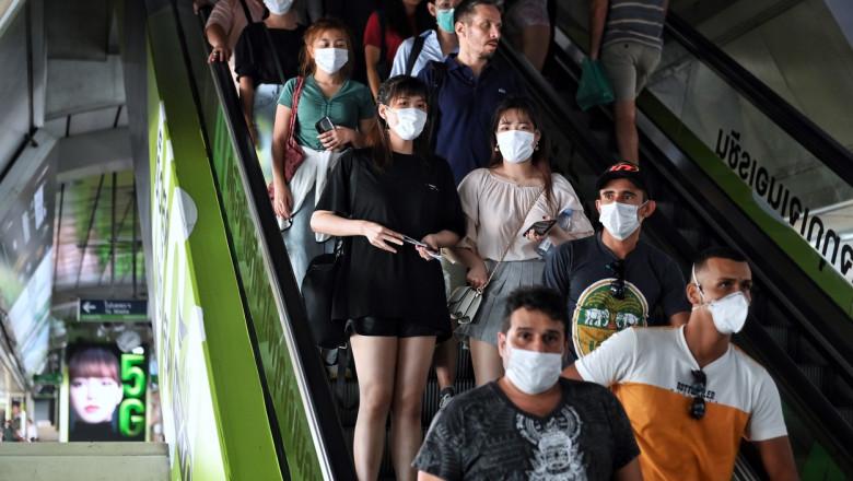 Mai multe persoane poarta masti pentru a se proteja