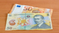 50 Euro banknote (EUR) and 50 Romanian lei banknote (RON) on wooden table.