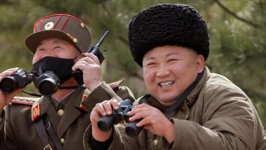 Kim Jong Un zâmbește, cu căciulă pe cap