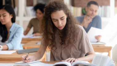 Teen girl studying with textbook writing essay learning in classroom