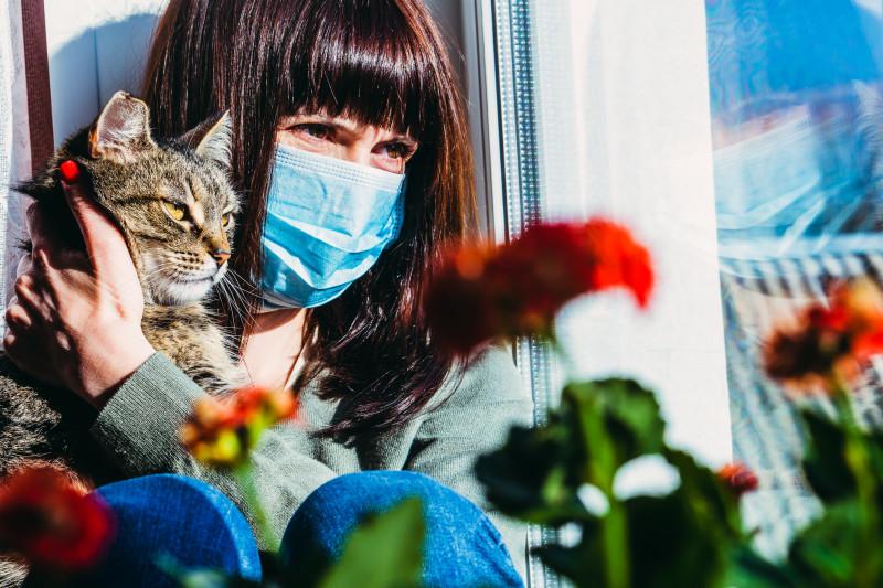 Femeie izolată în casă, cu mască pe figură, împreună cu pisica